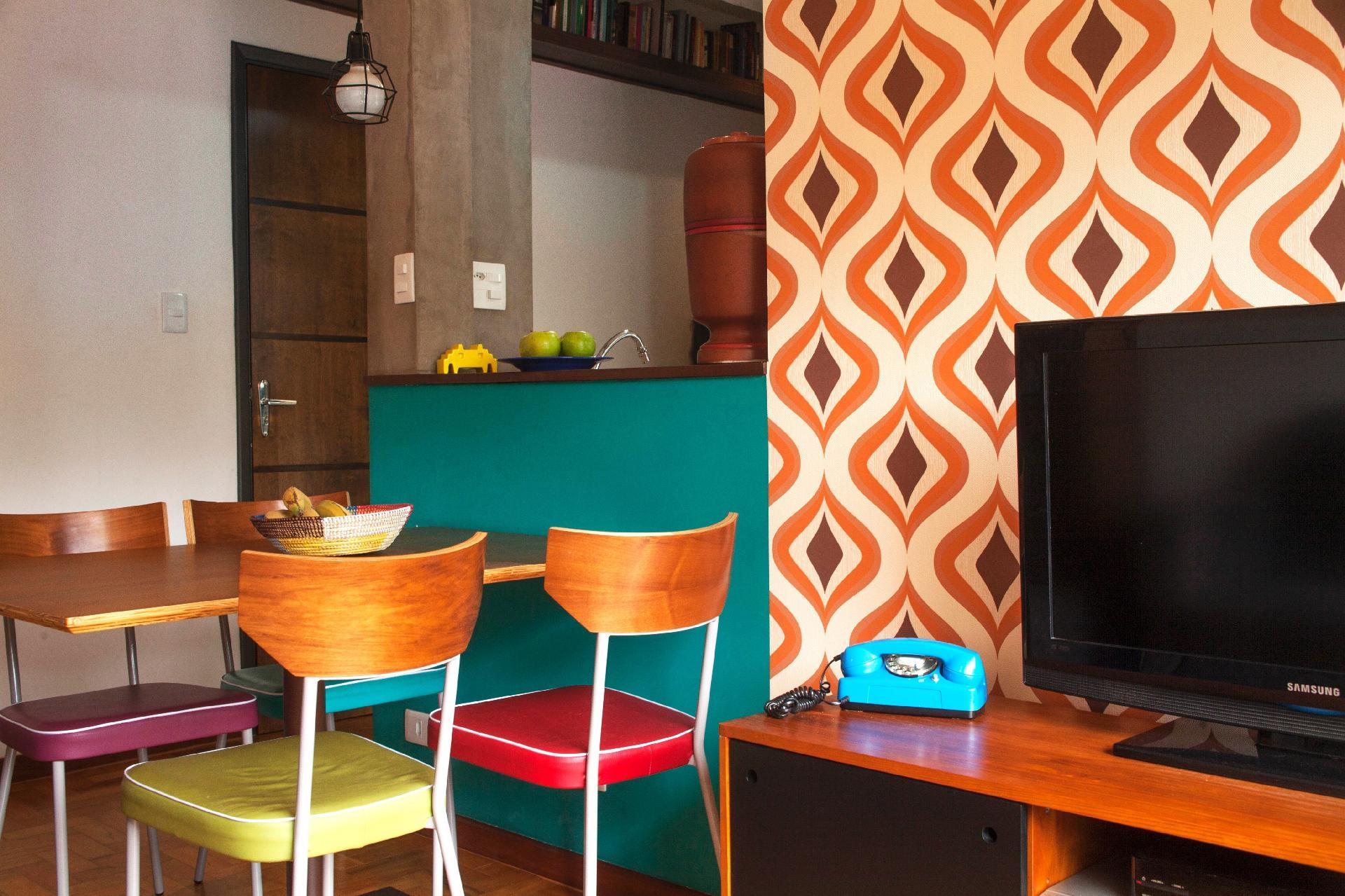 A mudança começou quando 'quebramos a parede da cozinha criando um balcão para integrar os ambientes  sociais', conta o arquiteto Fábio Borges, do escritório Dois Projetos. O teto foi mantido como na versão original, sem ser rebaixado em qualquer ponto. Pelo pé-direito um tanto alto, típico dos imóveis construídos nos anos 1970, os espaços parecem mais amplos