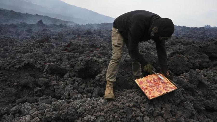 Chef cozinhando pizza em um fluxo de lava fresca do vulcão Pacaya, na Guatemala - AFP