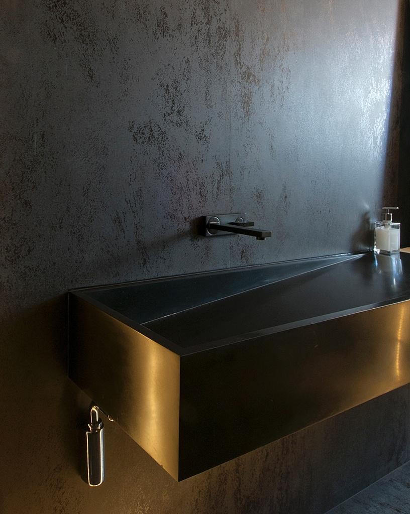 O lavabo desse apartamento em São Paulo ganhou uma aura futurista graças à louça preta (Deca) e ao revestimento das paredes que reproduz o padrão de aço patinável