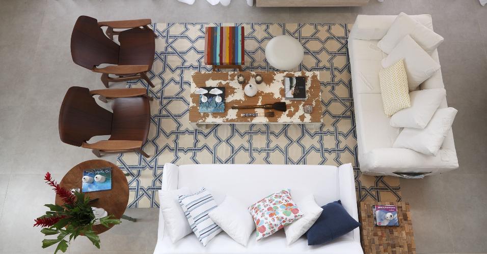 Nesta sala de estar no litoral norte de São Paulo, o tapete geométrico e a mesinha colorida se destacam no meio dos elementos neutros e clássicos. Ideia da In House Designers de Interiores