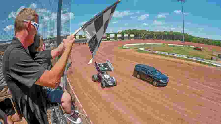 Piloto recebe adeus com bandeira em pista de corrida - Louis B. Ruediger