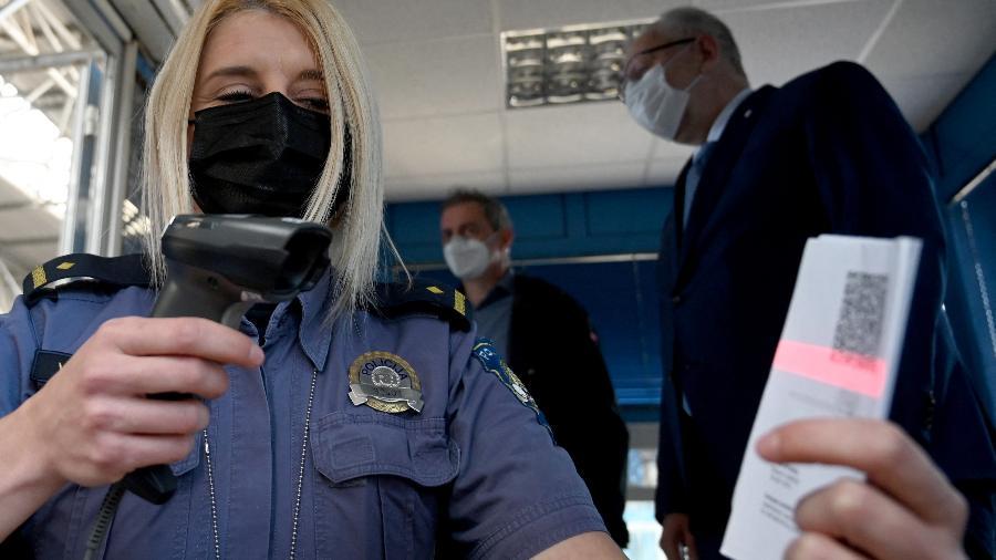 Policial verifica o QR code do passaporte da vacina - AFP