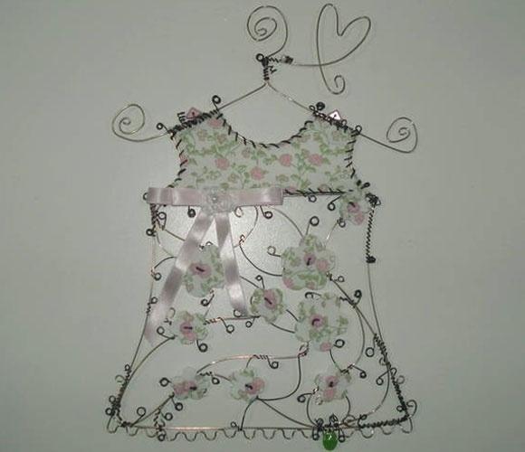 Enfeite aramado de vestido no cabide, da Feito Laço e Abraço (www.elo7.com.br/feitolacoeabraco). A peça mede 29 cm por 20 cm. R$ 220. Preço pesquisado em agosto de 2015 e sujeito a alterações