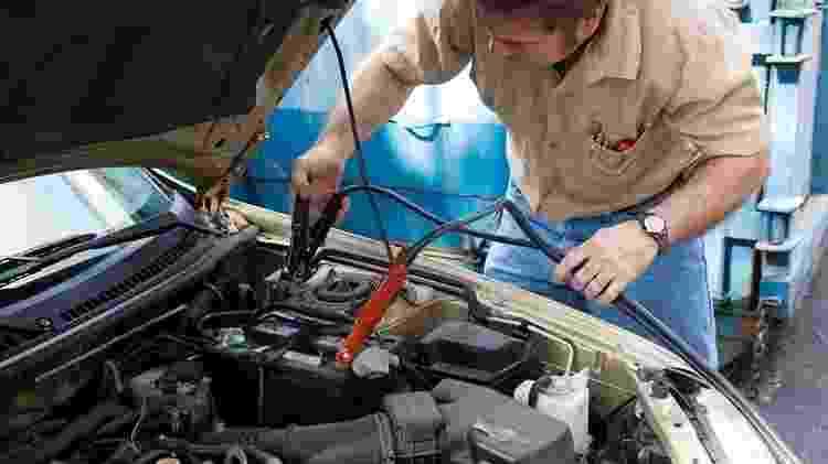 Mecânico trabalha em bateria de veículo - Shutterstock - Shutterstock