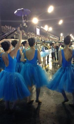 5.fev.2016 - A bailarina Rosana diz que a chuva não atrapalha e até ajuda a amenizar o calor. Ela já desfilou três vezes, mas nunca coreografada e com chuva. As meninas de vestido azul escuro usam sapatilha de meia ponta, mais difícil de escorregar. Mas a bailarina Isabela, de azul claro, usa sapatilha de ponta, mais arriscado escorregar na chuva.