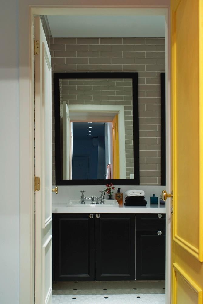 No banho da suíte, gabinetes (Florense) seguem o padrão em MDF microtexturado preto, enquanto o espelho tem moldura que o acompanha, na mesma cor. O piso é de pastilhas hexagonais preto e branco (Mazza). O estilo retrô é marca do projeto da D2N Arquitetura e Interiores para o Apartamento Higienópolis