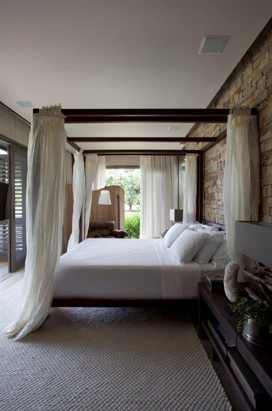 Na casa de praia criada por Debora Aguiar, a suíte do casal tem cama com dossel e fica encostada à parede em pedras. No quarto, as cores neutras que vão do