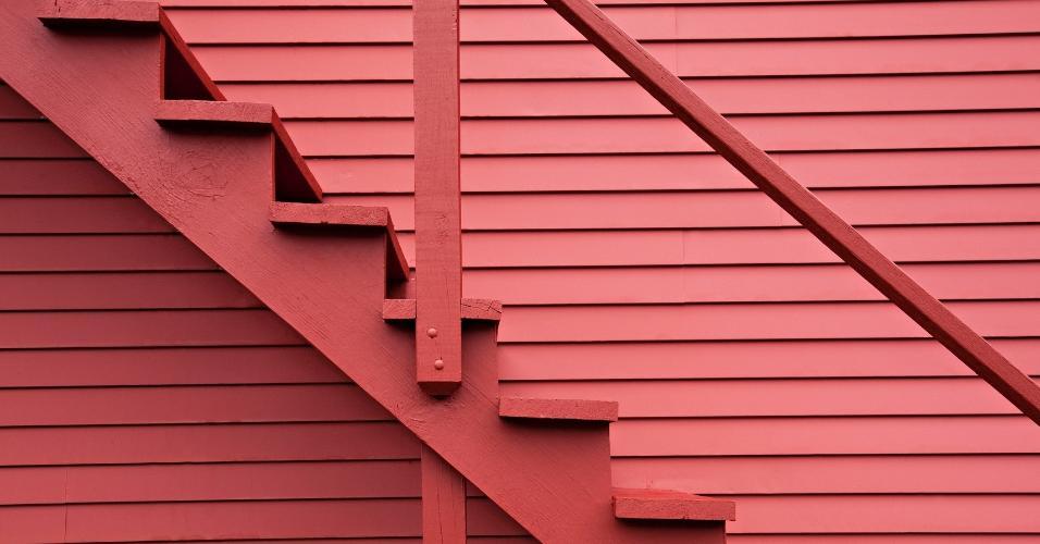 A escada reta instalada no exterior é uma das mais comuns no quesito construção, mas este exemplar foi valorizado pela cor vermelha também usada na parede, ao fundo. O corrimão não tem muitos detalhes, mas se encaixa perfeitamente na proposta arquitetônica
