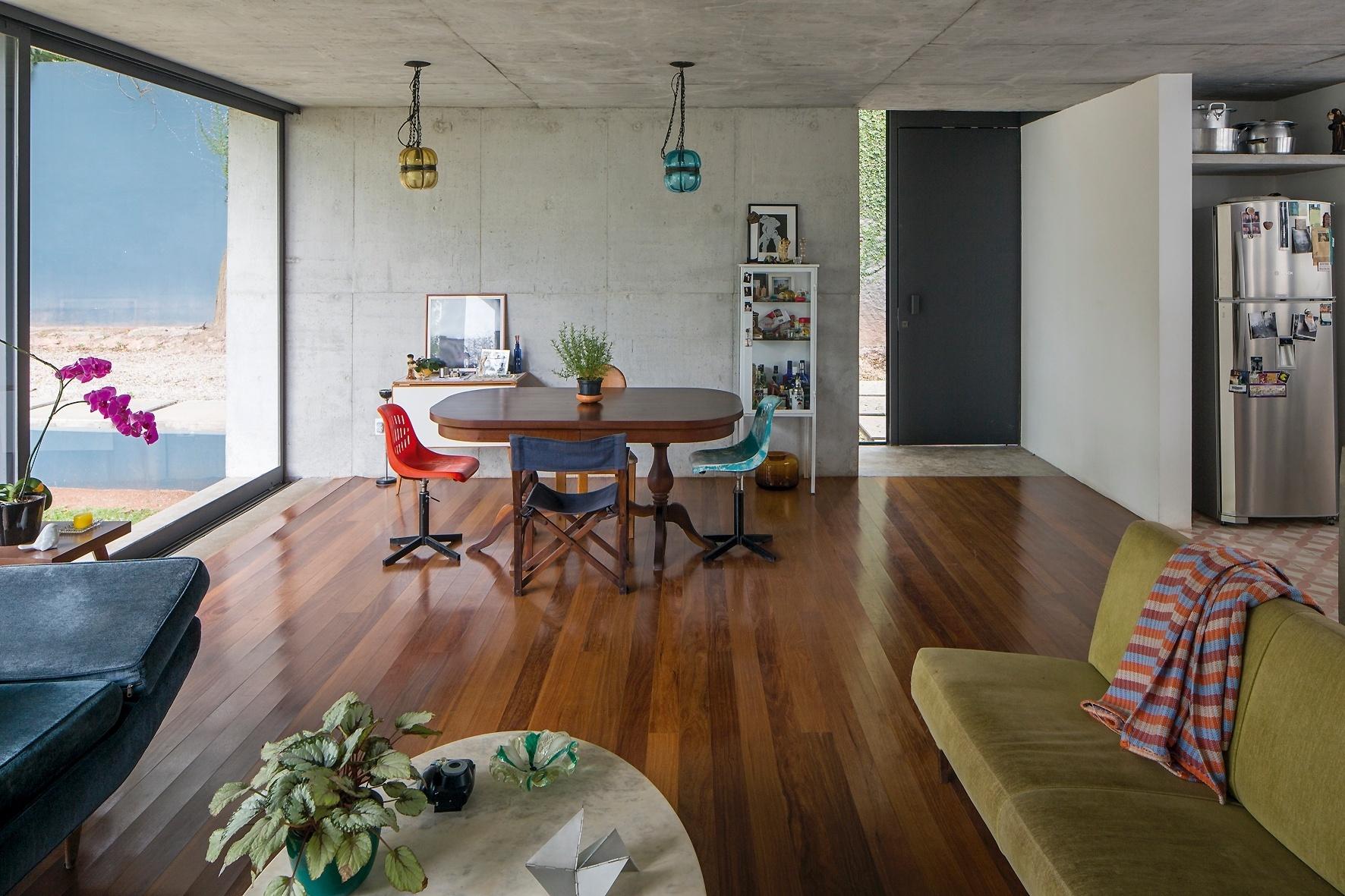 O living da casa LP, idealizada pelo escritório Metro Arquiteto, integra estar e jantar compostos com móveis despojados e dotados de pontos de cor. Ao fundo (e à dir.), o hall de entrada é delimitado pelo piso de concreto