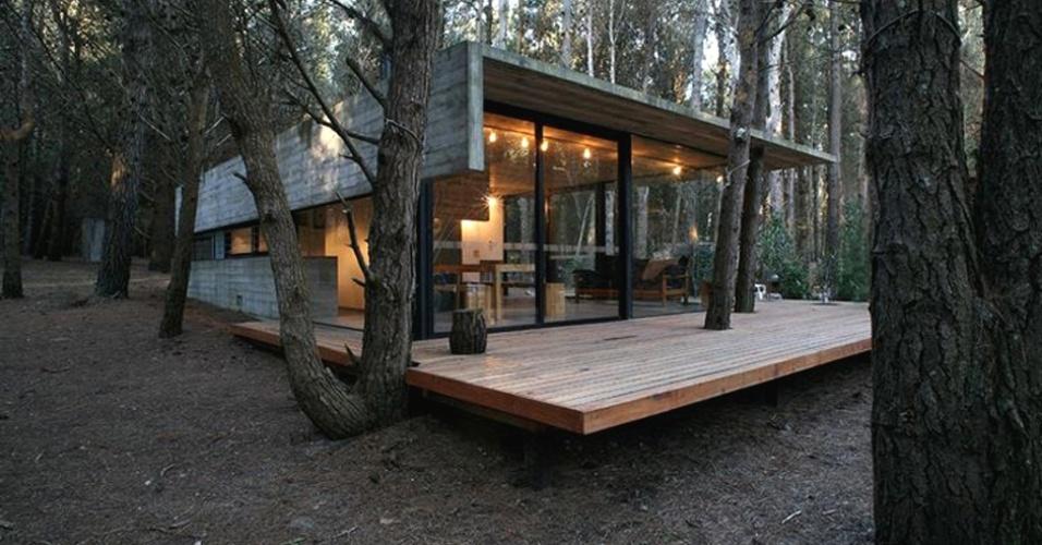 Localizado em Mar Azul, resort turístico próximo a Buenos Aires, Argentina, esta casa de veraneio com design do escritório BAK Arquitectos Asociados também incorporou a floresta local, através do deck e da cobertura em concreto com recortes para a passagem de troncos e galhos