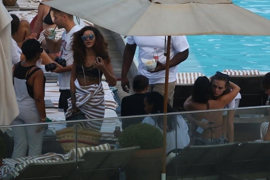 28.set.2015 - Rihanna come petiscos na piscina do hotel no Rio de Janeiro