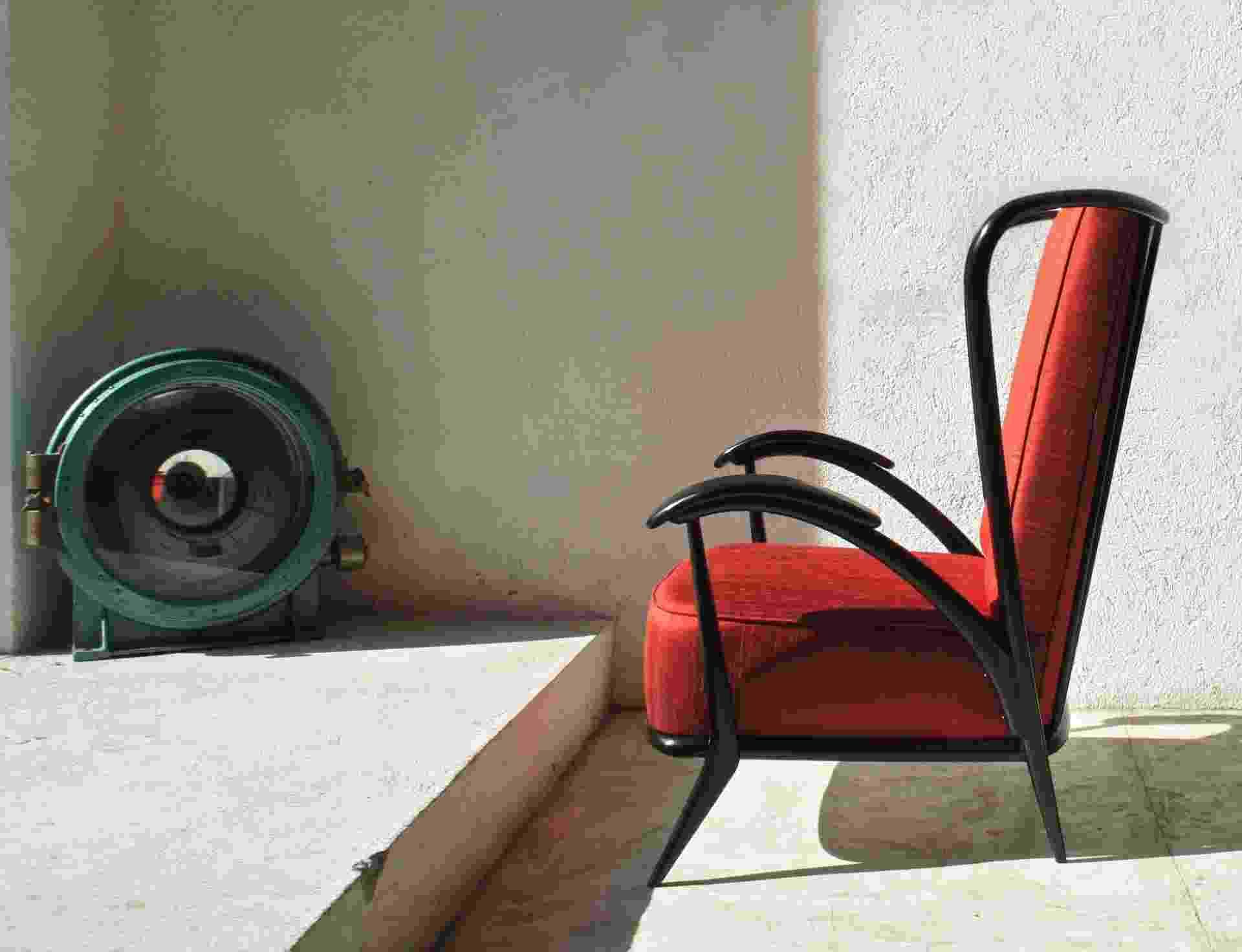"""Giuseppe Scapinelli desenvolve em 1954 uma releitura das famosas """"bergères"""". O móvel ebanizado tem espaldar alto e é esculpido em madeira. O estofamento foi feito com seda vermelha. A imagem foi reproduzida no livro """"Giuseppe Scapinelli 1950: o Designer da Emoção"""" e fez parte da edição nº 10, da revista Casa e Jardim (1954) - Divulgação"""