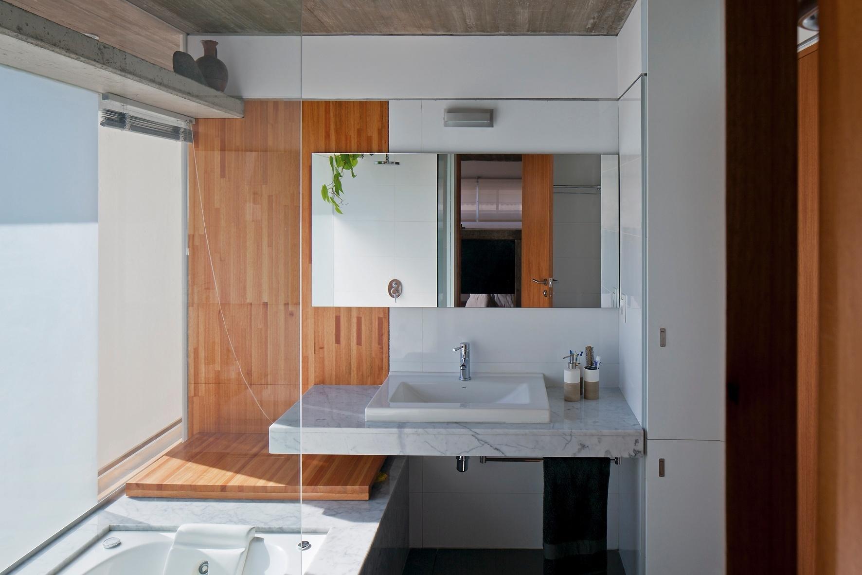 O banheiro principal tem sua privacidade garantida por folhas de vidro jateado, que protegem a banheira do corredor externo de circulação (no piso intermediário). Os acabamentos acompanham o ritmo da casa Ibiray: madeira, concreto aparente e mármore dominam o pespaço projetado pelos arquitetos Lucho Oreggioni e Sonia Prieto
