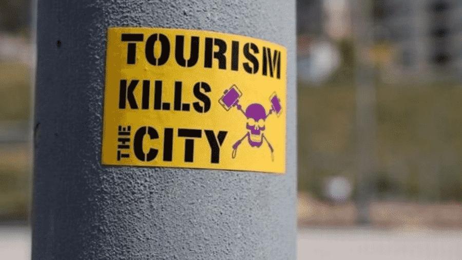 """""""O turismo mata a cidade"""", diz um adesivo colado em um poste, em Barcelona - GETTY IMAGES"""
