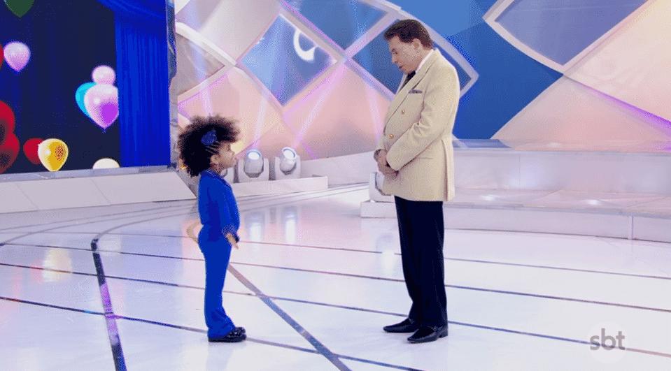 """Silvio Santos foi chamado por intrenautas de """"preconceituoso e racista"""" devido a comentários que fez sobre o cabelo afro de uma criança do Rio de Janeiro. O empresário e apresentador perguntou à menina se ela achava que estava bem com o cabelo, pois, na sua opinião, estava chamando atenção demais. - Reprodução/SBT.com.br"""