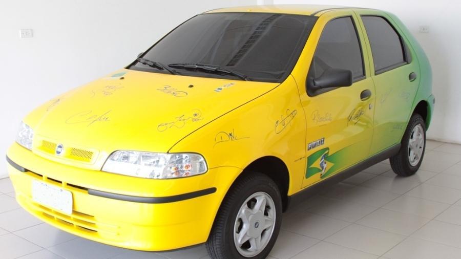Fiat Palio autografado por pentacampeões para a Fundação Cafu - Reprodução