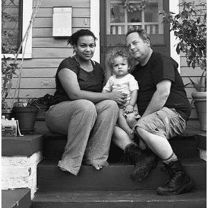 """A fotógrafa Donna Pinckley optou por fazer os cliques em preto e branco e pediu para o casal escrever qual foi o pior insulto que ouviram. """"Eu disse que uma mulher negra vivia com um homem branco nessa casa"""", ouviu o casal da imagem - Reprodução/Donna Pinckley"""
