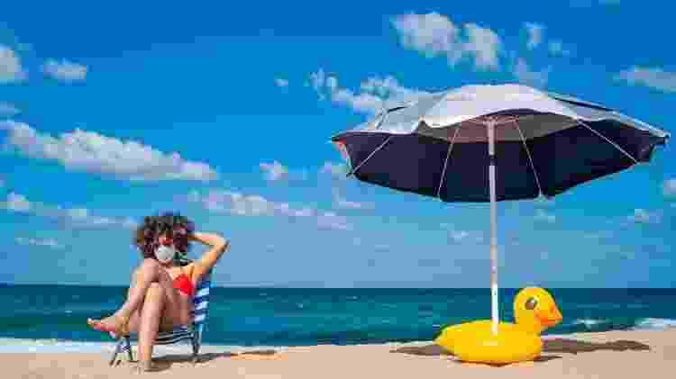 Mulher na praia com máscara - iStock - iStock