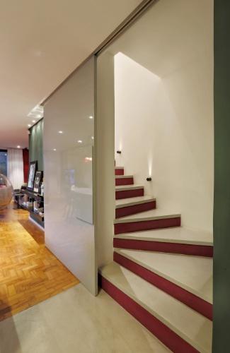 Quando aberta, a porta de correr dá acesso à escada que leva ao pavimento superior íntimo e esconde o armário para taças e louças. As escadas são revestidas com tecnocimento, mesmo material usado no piso da cozinha. O projeto de reforma é de Renata Popolo