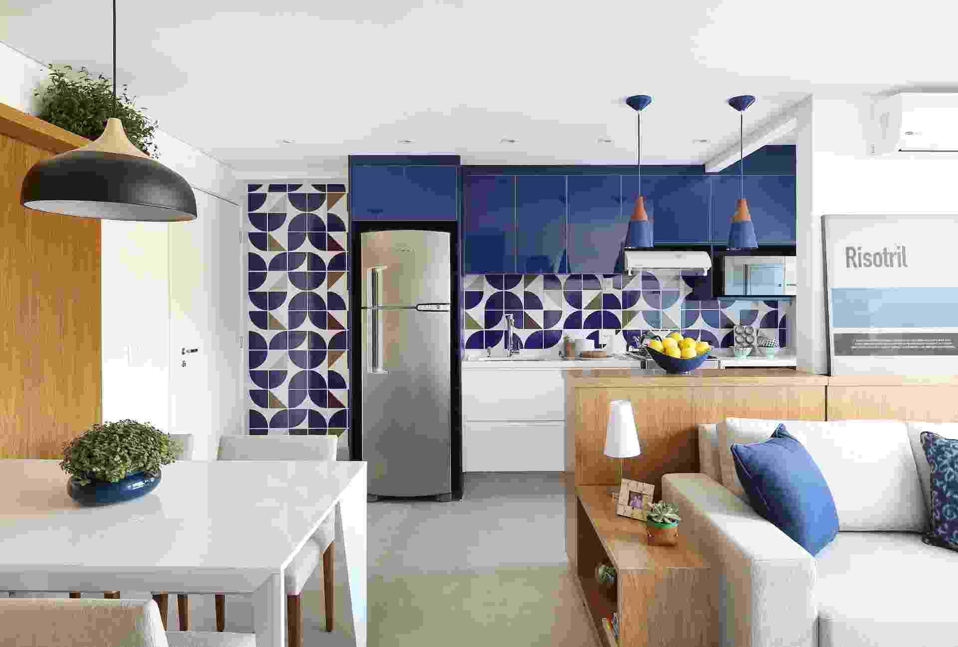 O Rio, a arquitetura moderna e as obras de Athos Bulcão inspiraram o escritório Samaia Arquitetura neste projeto do imóvel de 52 m². A retirada da parede que dividia sala e cozinha eliminou o corredor de entrada para o estar. Atrás do sofá, o aparador da cozinha serve de apoio para quadros. Já a madeira contrasta com o piso de porcelanato. Destaque para os azulejos (Lurca) da parede da cozinha - Mariana Orsi/ Divulgação