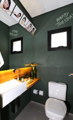 A mistura de materiais e cores cria uma atmosfera descontraída para o lavabo da casa Sumaré: nas paredes, pintura verde lousa; no piso, tecnocimento; madeira de demolição na bancada e cuba em Corian. As louças e os metais escolhidos pela arquiteta Renata Popolo são da Deca