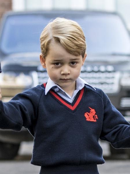 Príncipe George segura as mãos do pai e da diretora da escola - AFP