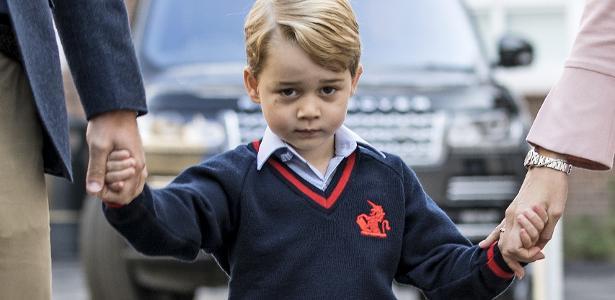 Príncipe George segura as mãos do pai e da diretora da escola