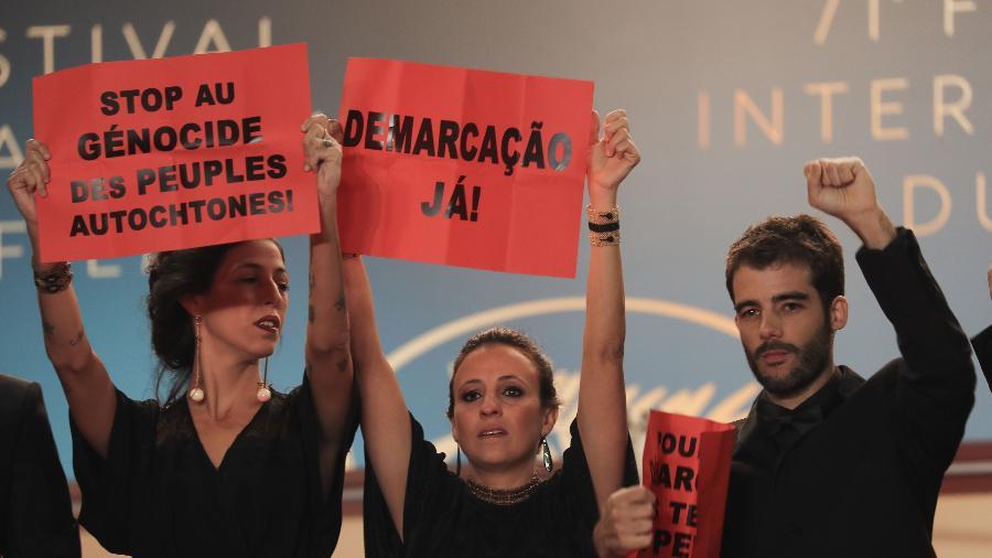 A produtora Isabella Nader e os diretores Renee Nader Messora e Joao Salaviza fazem prostesto em Cannes contra o genocídio indígena - AFP/ Valery HACHE