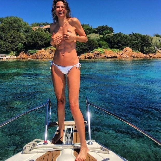 """19.set.2016- Luciana Gimenez volta e meia surge nas redes sociais à vontade demais com decotes, fendas e transparências, mas nesta segunda-feira (19), ela resolveu fazer mesmo um topless e compartilhar a imagem no Instagram. Na foto, a  apresentadora aparece sorridente com as mãos escondendo os seios durante um passeio de barco na Itália.""""Sardenha, me leva"""", escreveu Luciana na legenda, se referindo ao nome da ilha em que está naquele país da Europa"""