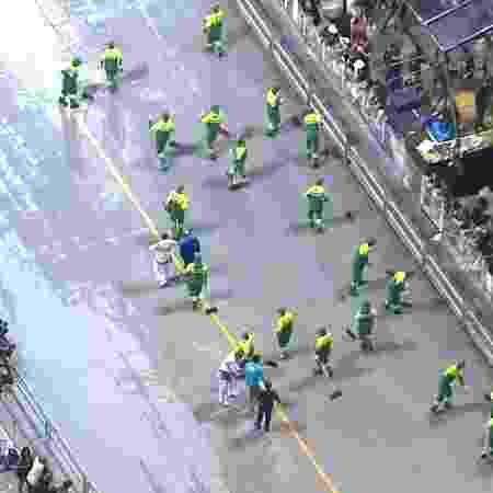 Funcionįrios tiveram que secar o sambódromo após passagem de carro da Vai-Vai, o que atrasou os śltimos desfiles da noite - Reproduēćo/TV Globo