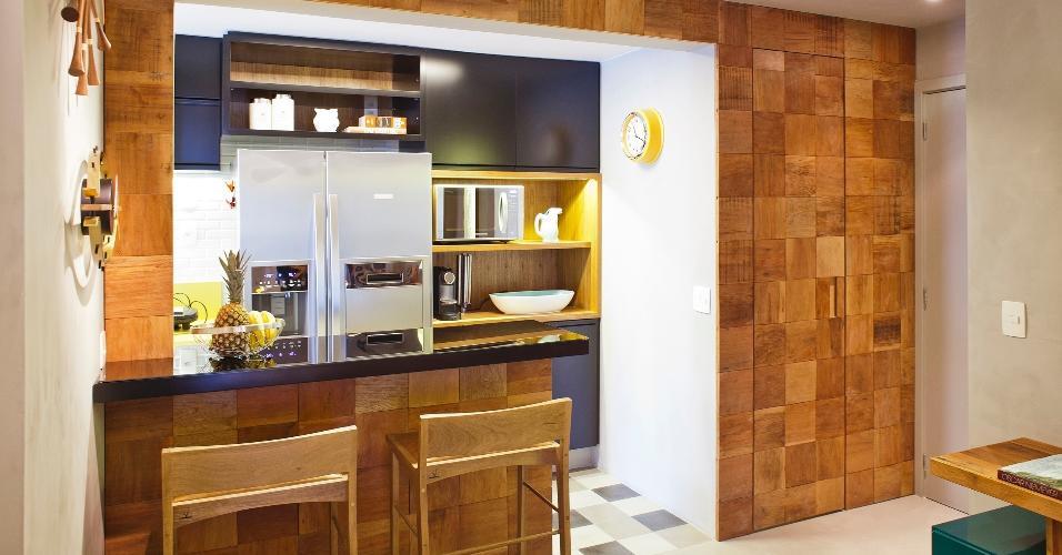 9 m². Ao abrir um grande vão para a sala, os profissionais da PKB Arquitetura deixaram a cozinha com formato de corredor mais fluida. Ainda foi possível criar um balcão para as refeições rápidas da família.