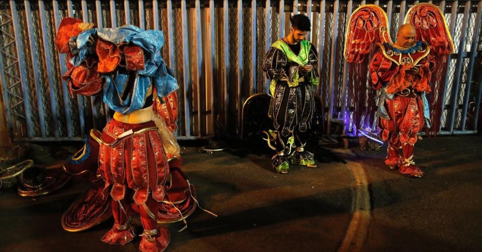 8.fev.2016 - Após desfilar, integrantes checam o celular antes mesmo de tirarem as fantasias, na Sapucaí