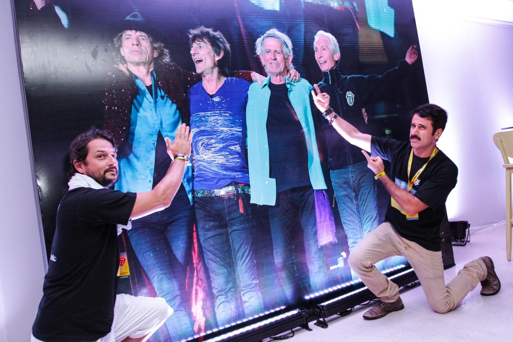 20.fev.2016 - Os atores Marcelo Serrado e Eriberto Leão fazem brincadeira com pôster da banda no camarote do show dos Rolling Stones no Maracanã, no Rio