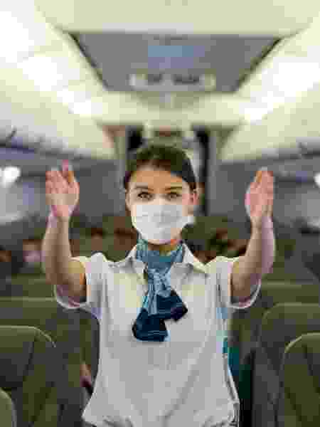 Comissária de bordo com máscara; viagem na pandemia - Getty Images - Getty Images