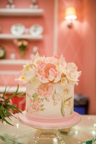 Pintado à mão, o bolo da aniversariante, da Pink Cake Box, tinha flores de baunilha, massa de pistache e recheio de ganache de chocolate