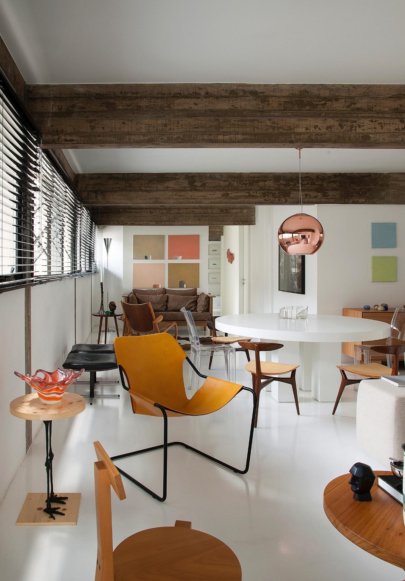 Junto à mesa (em primeiro plano), está uma cadeira Girafa, em madeira, assinada pela modernista Lina Bo Bardi (1914-92) e fabricada pela Marcenaria Baraúna. A poltrona em couro com estrutura de aço é do arquiteto Paulo Mendes da Rocha. Inusitada é a mesinha lateral (à esq.), do Estudio Manus: a peça em madeira tem pernas feitas com liga flexível que imitam um flamingo. Sobre ela está um vaso dos anos 50, em murano. A decoração foi desenvolvida pelo arquiteto Marcos Bertoldi, para o apê Itaim