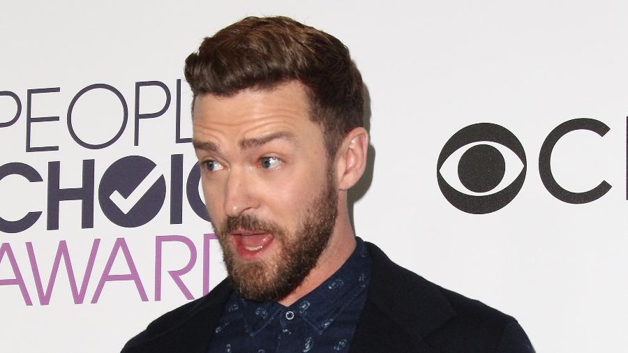 """18.jan.2016 - Justin Timberlake carrega seus dois troféus de cristal do People""""s Choice Awards. O cantor ganhou como melhor cantor e melhor música por """"Can""""t Stop The Feeling"""", trilha sonora da animação """"Trolls"""" - Tommaso Boddi/AFP"""