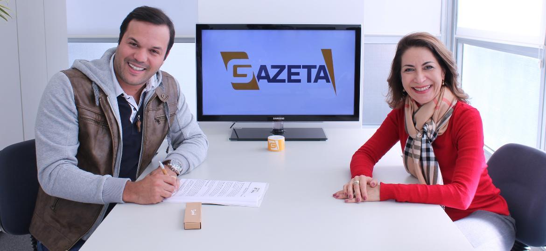 Padre Alessandro Campos assina contrato com a Gazeta ao lado da superintentende de programação, Marinês Rodrigues - Beatriz Vecchi/TV Gazeta
