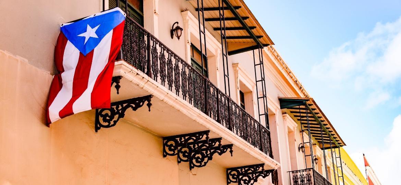 Bandeira de Porto Rico hasteada em rua de bairro histórico da capital - iStock