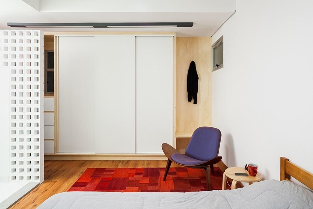 No dormitório, a marcenaria também seguiu o conceito de neutralidade com acabamento em laminado branco. A poltrona Shell do designer dinamarquês Hans J. Wegner compõe com o tapete quadriculado em tons de vermelho, levando cor ao espaço. Quem assina o projeto de reforma para o apartamento em São Paulo (SP) é o escritório Grupo Garoa Arquitetos