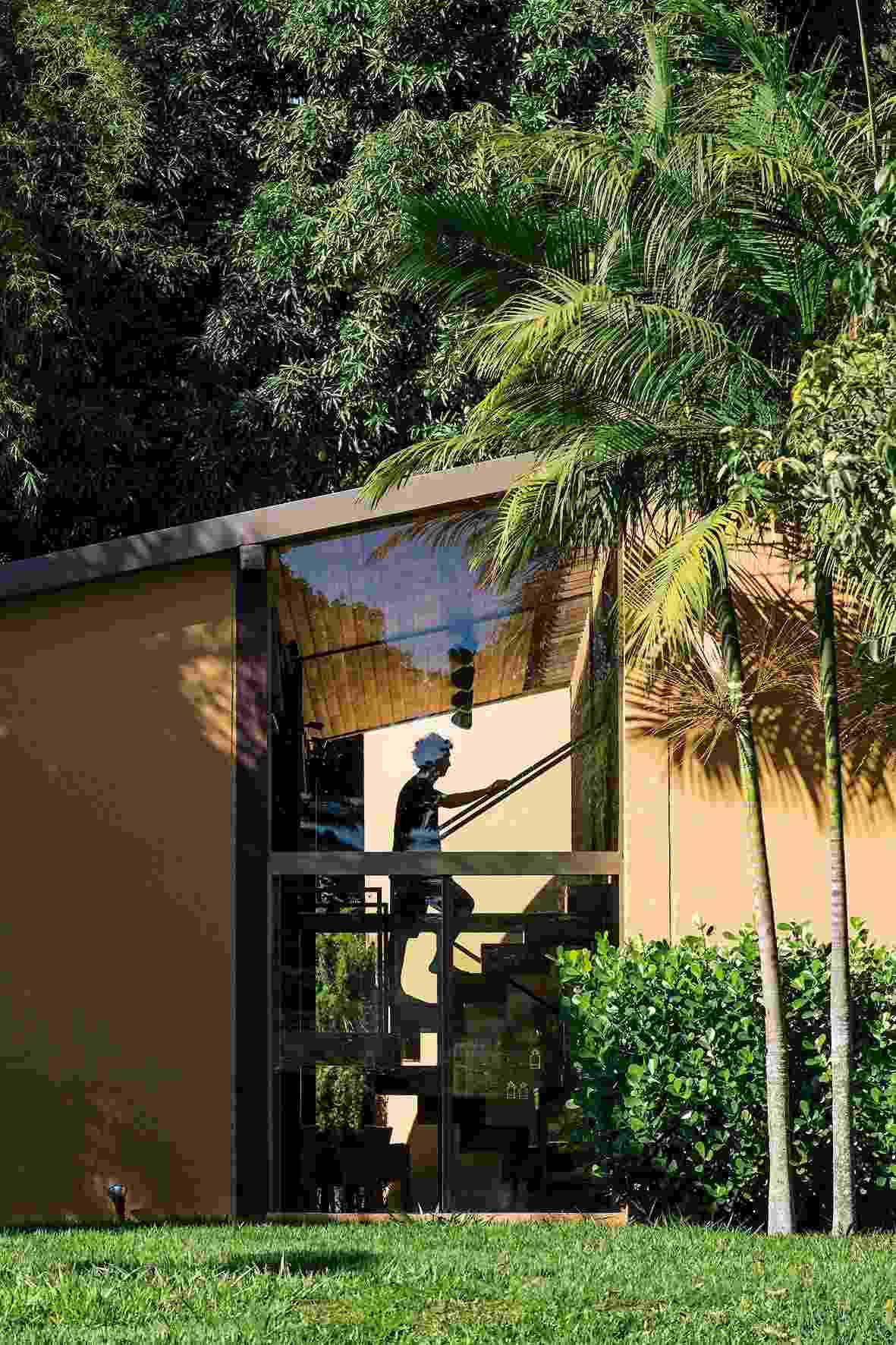 A escada de acesso aos dormitórios recebe luz natural através do recorte na lateral da fachada, com fechamento em vidro. A casa Várzea foi projetada pelo arquiteto Gustavo Penna e fica em Minas Gerais - undefined