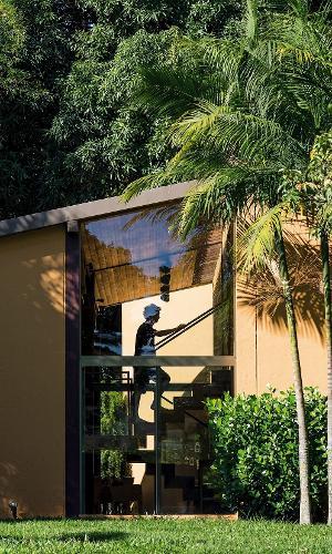 A escada de acesso aos dormitórios recebe luz natural através do recorte na lateral da fachada, com fechamento em vidro. A casa Várzea foi projetada pelo arquiteto Gustavo Penna e fica em Minas Gerais