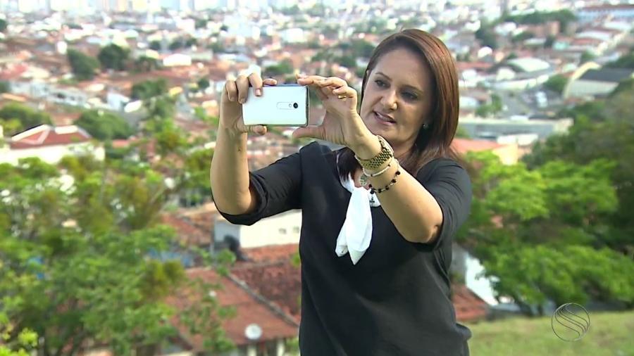 A repórter Carla Suzanne, da TV Sergipe, afiliada da Globo, ensina os telespectadores a filmar com o celular na horizontal - Reprodução/TV Sergipe
