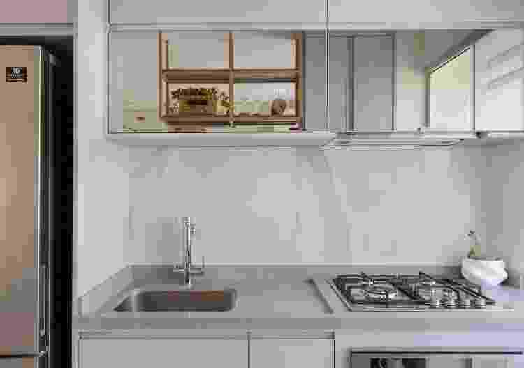 A partir do revestimento de porcelanato polido marmorizado aplicado no frontão da pia, os arquitetos especificaram o espelho para que resultasse em leveza e modernidade - Fernando Crescenti - Fernando Crescenti