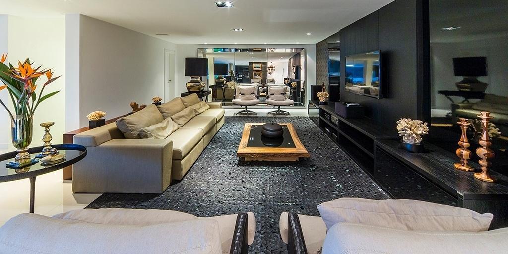Na casa em Balneário Camboriú (SC), a ampla sala conta com mais de 40 m² e está integrada ao jantar e à cozinha. Sobre uma base neutra, composta pelo piso de porcelanato e pelas paredes brancas, os arquitetos do EB Arquitetura projetaram interiores elegantes, com mix de texturas e peças pretas