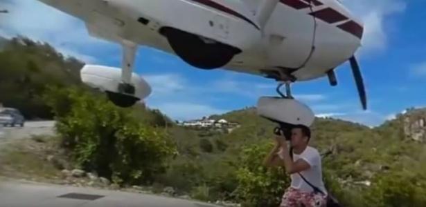 O trem de pouso da aeronave quase atinge a cabeça do fotógrafo - Reprodução/Youtube
