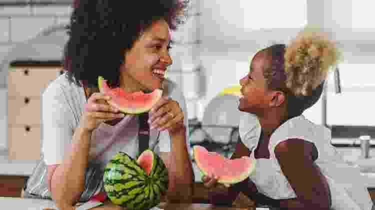 mãe filha comendo fruta; melancia - iStock - iStock