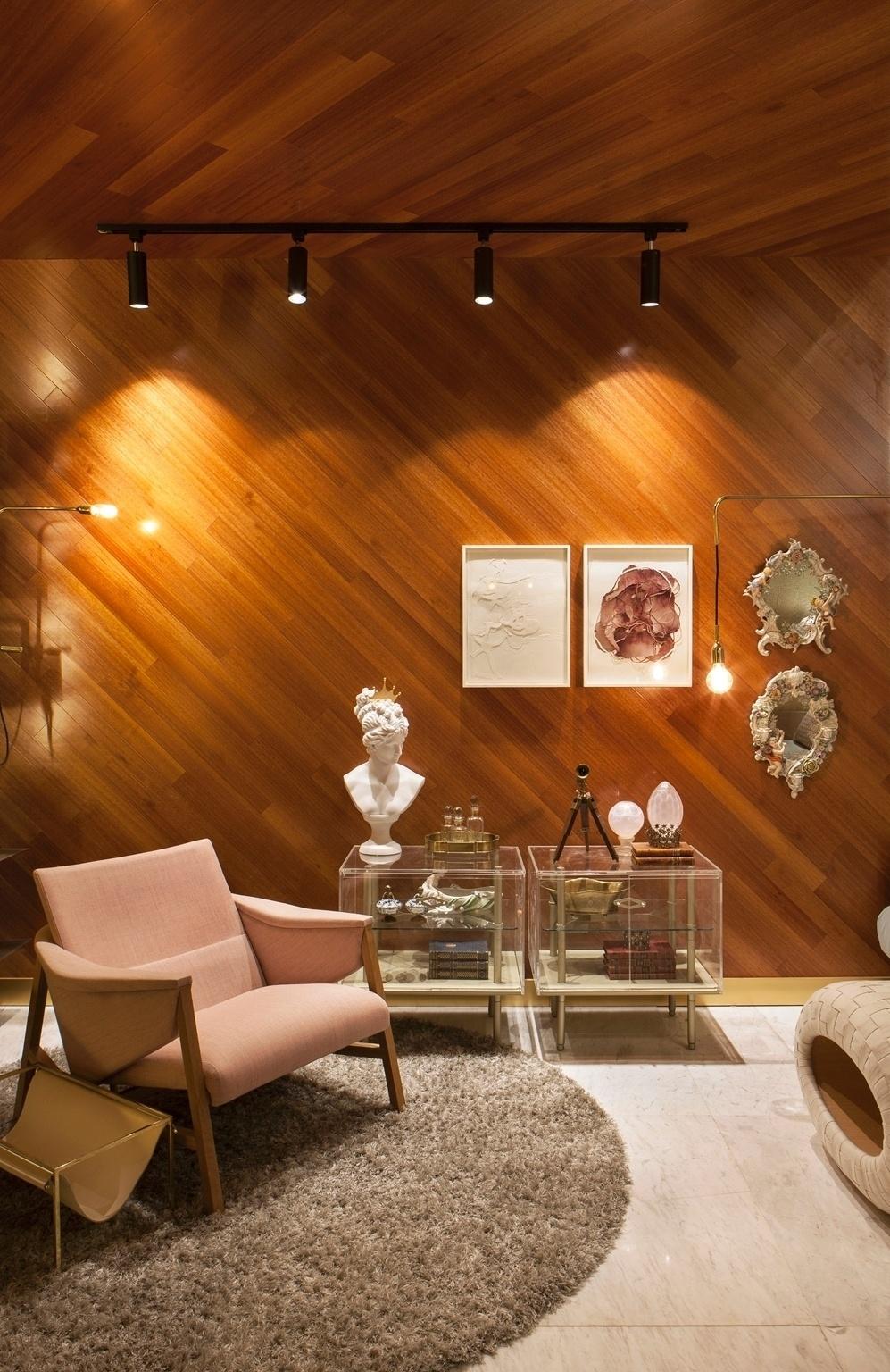 Casa Cor PE - 2016: na Sala de TV, projetada por Mariana Russo e Fernanda Ventura, a madeira cumaru utilizada no revestimento do teto e da parede foi o ponto de partida para a decoração. Os detalhes clássicos - como os espelhos (à dir.) - são parte do arquivo pessoal das arquitetas. Estes elementos convivem com o toque contemporâneo dado pelos criados-mudos de acrílico e móveis com ares modernos