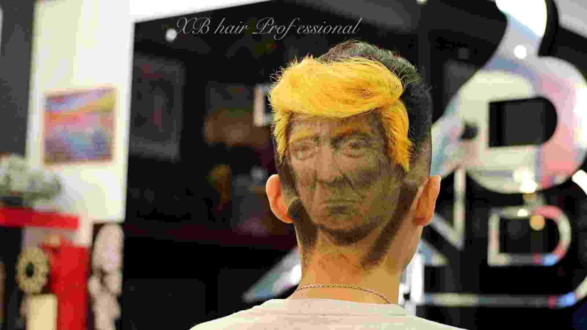 Para ter o Donald Trump estampado na cabeça, o cabeleireiro pinta parte dos fios de alaranjado, formando o característico topete. Os traços do rosto são cuidadosamente desenhados também - Reprodução/Facebook