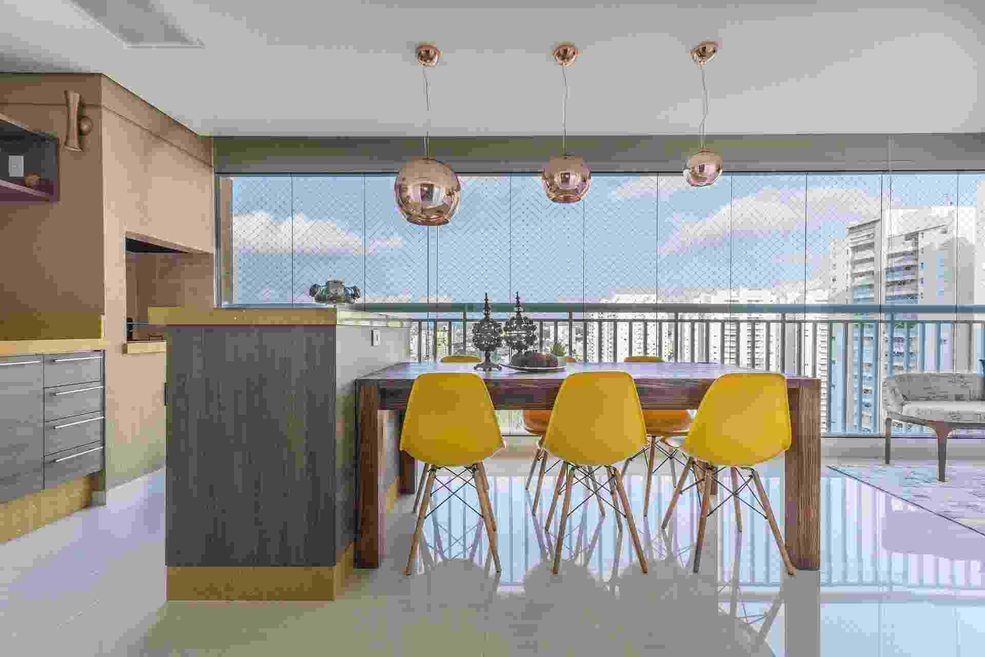 Como esta varanda tem dimensões generosas, a designer de interiores Silvana Borzi empregou uma ampla bancada junto à área da churrasqueira, com mesa de jantar integrada. As cadeiras criadas por Charles e Ray Eames em amarelo e os pendentes de cobre se destacam na decoração neutra - Henrique Ribeiro/ Divulgação